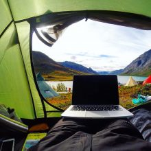 Laptop on a sleeping bag with an open tent door