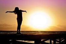Woman standing on a dock at sunset with her arms outstretched